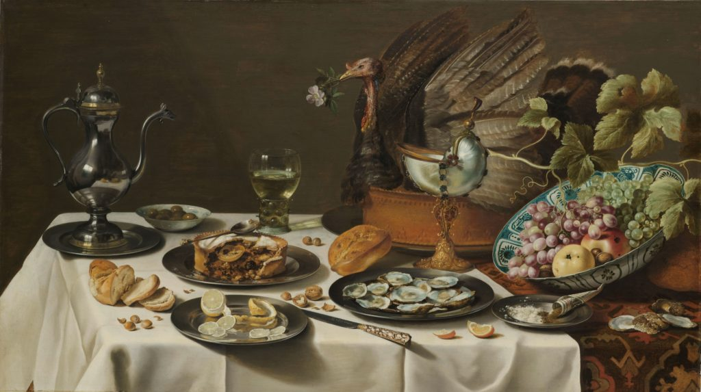 Still life focusing on pie decorated with head, wings and tail of unidentified bird.